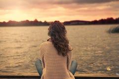 La donna sta sedendosi nel lago immagine stock