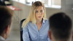 La donna sta sedendosi nell'ufficio che ha l'intervista o riunione del lavoro stock footage