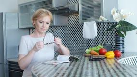 La donna sta sedendosi nella cucina alla tavola e sta leggendo una ricetta per un piatto video d archivio
