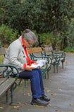 La donna sta sedendosi su un banco e su una mappa d'esplorazione della città Fotografia Stock