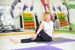 La donna sta sedendosi sul pavimento e sull'allungamento Immagini Stock