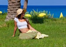 La donna sta sedendosi sull'erba verde vicino al mare Fotografia Stock