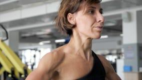 La donna sta sollevando il bilanciere che fa gli esercizi per le spalle archivi video