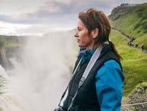 La donna sta stando ad una cascata di Gullfoss - Islanda Immagini Stock Libere da Diritti