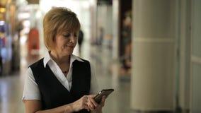 La donna sta stando nel corridoio aspettante dell'aeroporto che esamina sorridere del telefono cellulare video d archivio