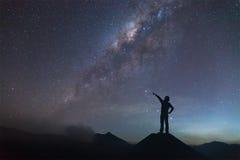 La donna sta stando sulla collina e sta indicando la Via Lattea Fotografie Stock