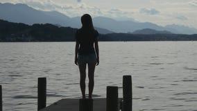 La donna sta sul pilastro del lago alpino da solo archivi video