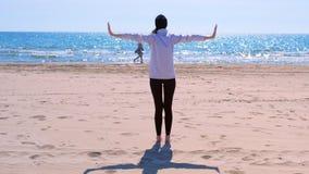 La donna sta sulle armi della spiaggia del mare della sabbia fuori ai lati fa la vista di esercizio di yoga indietro stock footage
