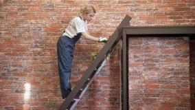 La donna sta sulle scale che dipingono il punto marrone della pittura all'interno video d archivio