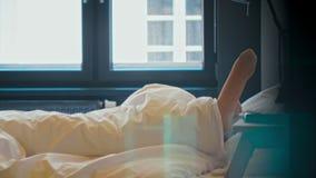 La donna sta svegliando in camera da letto, nell'allungamento e nell'uscire del letto di mattina stock footage
