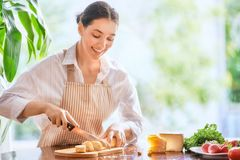 La donna sta tagliando il pane ed il formaggio fotografie stock