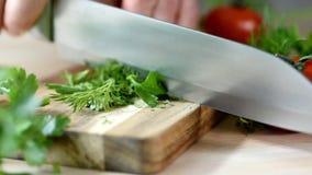 La donna sta tagliando il prezzemolo, coltello di verdi sul bordo di legno archivi video