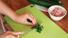 La donna sta tagliando l'aneto fresco nella cucina sulla tavola di legno archivi video