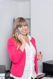La donna sta telefonando nell'ufficio Fotografie Stock Libere da Diritti