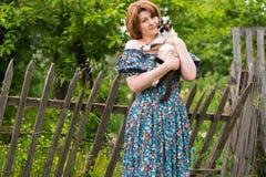 La donna sta tenendo il gatto contro lo sfondo del recinto rurale Fotografia Stock
