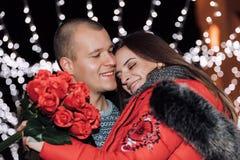 La donna sta tenendo le rose e sta sorridendo mentre abbracciava l'uomo immagine stock libera da diritti