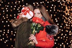 La donna sta tenendo un contenitore e le rose di regalo e sta sorridendo mentre abbracciava l'uomo fotografia stock