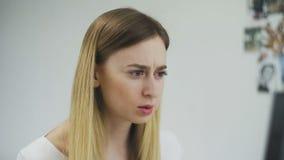 La donna sta usando la spazzola alle sopracciglia di tintura, quindi ha frustrato l'esame in dello specchio archivi video