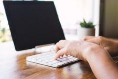 La donna sta utilizzando una compressa e una tastiera di battitura a macchina Fotografie Stock Libere da Diritti