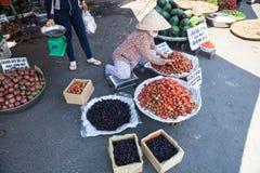 La donna sta vendendo la fragola ed il gelso al mercato bagnato immagine stock