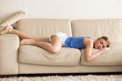 La donna stanca allunga fuori e dorme sul sofà Immagine Stock