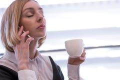 La donna stanca beve il caffè e chiama fotografie stock