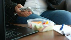 La donna stante a dieta di affari in vestito ha il cibo dello spuntino sano della frutta dalla scatola di pranzo ed esame dello s archivi video