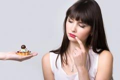 La donna stante a dieta è offerta il dolce Immagini Stock Libere da Diritti
