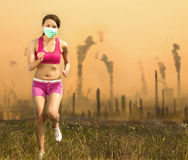 La donna stava indossando una maschera e un funzionamento sull'inquinamento atmosferico Immagini Stock Libere da Diritti