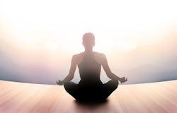 La donna stava meditando nella mattina e nei raggi di luce su paesaggio Immagine Stock