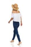 La donna in Straw Hat Walking Rear View ha isolato Immagini Stock