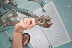 La donna stringe il rubinetto dell'aeratore del dado, facendo uso della chiave inglese Immagini Stock
