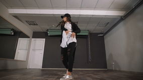 La donna in studio vuoto prende le lezioni di dancing È vestita in una camicia libera con un capo, sulla testa di lei un cappucci stock footage