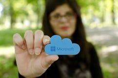 La donna su fondo vago raggiunge fuori la tenuta dell'icona di Microsoft Windows OneDrive Immagini Stock