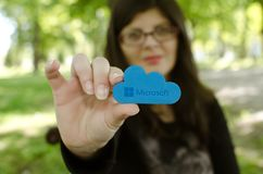 La donna su fondo vago raggiunge fuori la tenuta dell'icona di Microsoft Windows OneDrive Immagine Stock