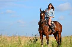 La donna su un cavallo nel campo Fotografie Stock Libere da Diritti