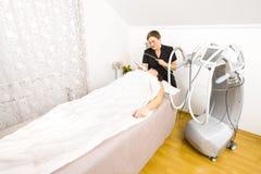 La donna subisce i trattamenti del fronte alla clinica di bellezza Immagini Stock