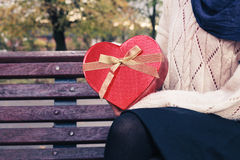 La donna sul banco di parco con cuore ha modellato la scatola Fotografia Stock