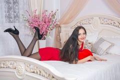 La donna sul letto che tiene un cuore della peluche Immagini Stock