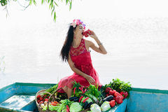 La donna sulla barca con le verdure mangia il pepe Fotografia Stock