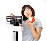 La donna sulla scala del peso sembra confusa Fotografie Stock