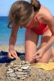 La donna sulla spiaggia costruisce la casa dai ciottoli Fotografia Stock
