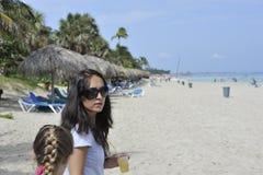 La donna sulla spiaggia sta esaminando indietro la macchina fotografica immagini stock