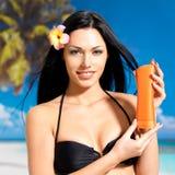 La donna sulla spiaggia tiene la bottiglia arancio della lozione di tan di sole. Fotografia Stock