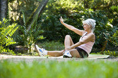 La donna sulla stuoia che fa l'allungamento si esercita all'aperto Fotografia Stock Libera da Diritti