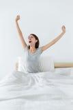 La donna sveglia all'allungamento della mano e di mattina Immagine Stock