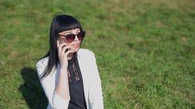 La donna sveglia con gli occhiali da sole ed i capelli lunghi sta utilizzando il dispositivo mobile che gode dei raggi di sole e  archivi video