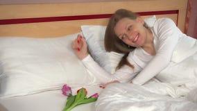 La donna sveglia e trova i fiori del tulipano macchina fotografica sorridente e di sguardo femminile felice archivi video