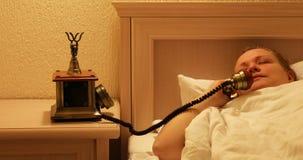 La donna, svegliata dalla telefonata, sta parlando sul telefono stock footage