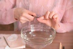 La donna taglia la cuticola con la pinza Fa il manicure lei stessa Mani del primo piano Strumenti del manicure sulla tavola Fotografia Stock